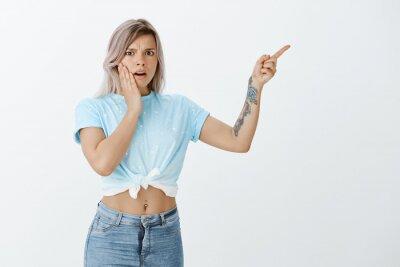 Portret niepewnej, zszokowanej atrakcyjnej kobiety o jasnych włosach z tatuażem na ramieniu, marszcząc brwi z niechęci, trzymając rękę na policzku i wskazując na prawy górny róg, będąc rozczarowanym i
