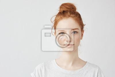 Fototapeta Portret piękna rudzielec dziewczyna ono uśmiecha się patrzejący kamerę.