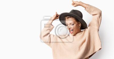 Fototapeta Portret piękna uśmiechnięta dziewczyna w kapeluszu i być ubranym trykotowego pulower na białym tle. Kobieta z jaskrawymi emocjami. Jesienna koncepcja mody.