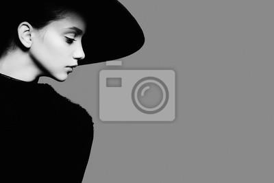 Fototapeta Portret pięknej dziewczyny w kapeluszu w profilu, pozowanie w studio, czarno-biały