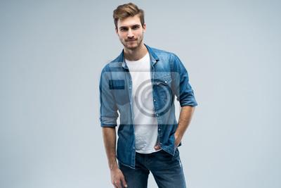 Fototapeta Portret stylowy, oszałamiający mężczyzna w dżinsowym stroju stoi na szarym tle.