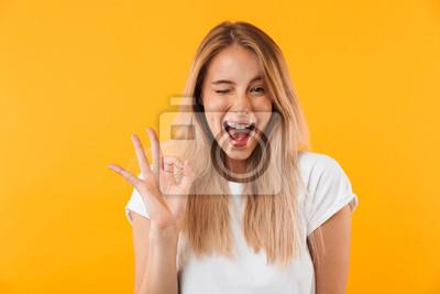 Fototapeta Portret szczęśliwa młoda blondynki dziewczyna pokazuje ok gest