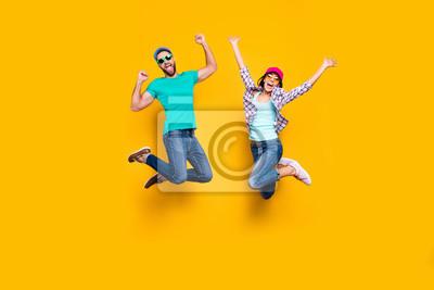 Fototapeta Portret szczęśliwy pomyślny pary doskakiwanie z nastroszonymi pięściami świętuje zwycięstwo jest ubranym drelichowego strój odizolowywającego na jaskrawym żółtym tle. Koncepcja sukcesu powodzenia ener