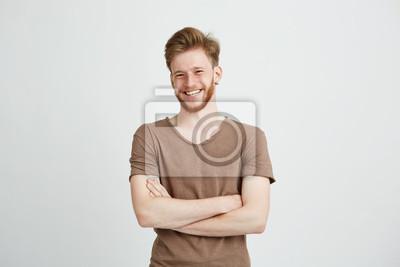 Fototapeta Portret szczęśliwy wesoły młody człowiek z brodą uśmiecha patrząc na kamery z skrzyżowanymi ramionami na białym tle.