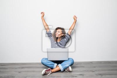 Fototapeta Portret szczęśliwych potomstw mieszanych ras kobiety kędzierzawy obsiadanie na podłoga z laptopem i świętuje wygranę