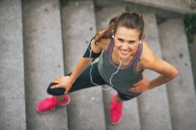 Fototapeta Portret uśmiecha się na zewnątrz Młoda kobieta fitness w mieście