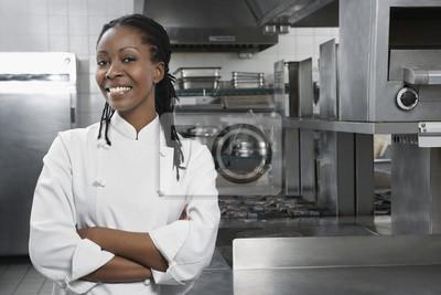 Fototapeta Portret uśmiechnięta kobieta kucharz z rękami skrzyżowanymi w kuchni