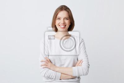 Fototapeta Portret wesołej atrakcyjne młoda kobieta w longsleeve stałego z bronią przekraczane i uśmiecha się samodzielnie nad białym tle Wygląda na pewność
