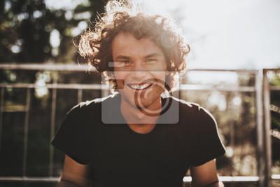 Fototapeta Portret zbliżenie zewnątrz przystojny piegowaty uśmiechnięty mężczyzna z kręconymi włosami, pozowanie do reklamy społecznej, na ulicy miasta na zachód słońca światło słoneczne z miejsca na kopię dla i