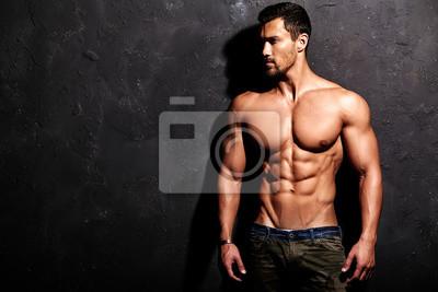 Fototapeta Portret zdrowych przystojny silne Athletic Man Fitness Model stwarzających w pobliżu ściany ciemnoszarym