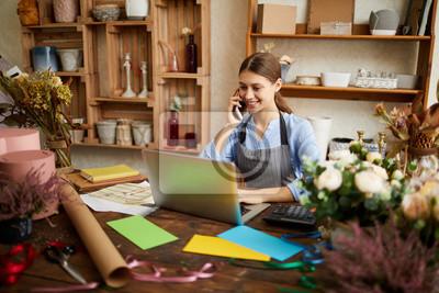 Fototapeta Portret żeński małego biznesu właściciel używa laptop i mówienie telefonem w kwiatu sklepie, kopii przestrzeń