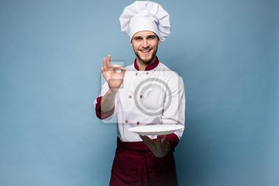 Fototapeta Positive professional happy man chef showing tasty ok sign isolated on light blue.
