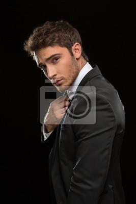 Fototapeta Poważne przystojny biznesmen w kolorze na czarnym tle