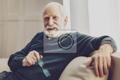 Fototapeta Pozytywne nastawienie. Szczęśliwy pozytywny człowiek uśmiecha się trzymając okulary w dłoniach