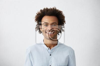 Fototapeta Pozytywny facet z afrykańskich fryzur i ciemnej skóry na sobie elegancki białą bluzkę szukających wesoło do aparatu samodzielnie na białym tle. Młody ciemnoskóry mężczyzna z uśmiechem odziewał się ele