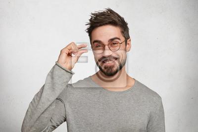 Fototapeta Pozytywny przystojny mężczyzna ze stylowym uczesaniem, ubrany w dorywczo sweter, pokazuje coś bardzo małe lub małe, będąc w dobrym nastroju, stanowi przeciwko białym tle betonu. Młodzi modni męscy ges