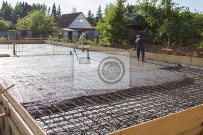 Fototapeta pracownik wyrównywania świeżej płyty betonowej za pomocą specjalnego narzędzia roboczego