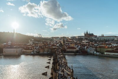 Prague, Czech Republic - March, 20th, 2019: Aerial view of the Charles Bridge, with a crowd crossing the Vltava river, the city in the background, a wonderful sunset and an incredible sky.