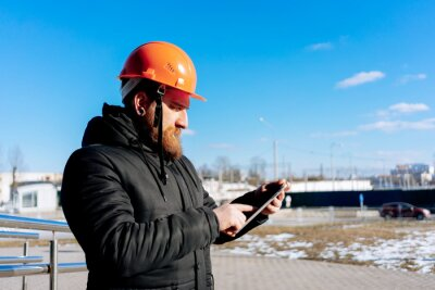 Fototapeta Pretty man - specialist civil engineer at orange hard hat is controls his project (outdoors). Blue sky and modern architecture (buildings) on background. Sunny day.