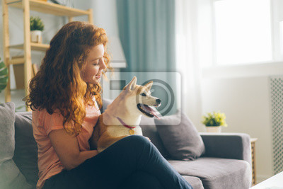 Fototapeta Pretty redhead woman is hugging cute doggy sitting on couch in apartment smiling enjoying beautiful day with beloved animal. People and pets concept.