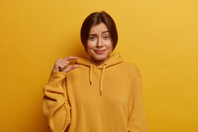 Fototapeta Pretty young European woman shows small size, demonstrates tiny measure, speaks about amount, dressed inn casual hoodie, shapes little object, isolated on yellow background. Body language concept.