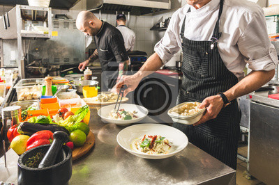 Fototapeta Professional chef cooking in the kitchen restaurant at the hotel, preparing dinner. A cook in an apron makes a salad of vegetables and pizza.