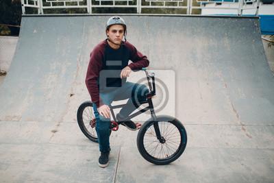 Fototapeta Professional young sportsman cyclist with bmx bike at skatepark