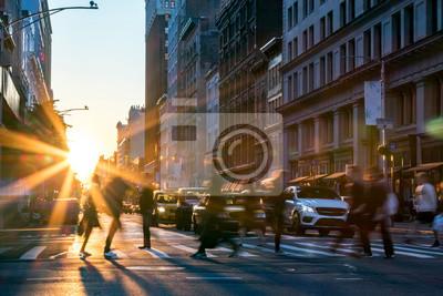 Fototapeta Promienie słońca świecą na ruchliwych ludzi przechodzących przez skrzyżowanie w Midtown Manhattan w Nowym Jorku