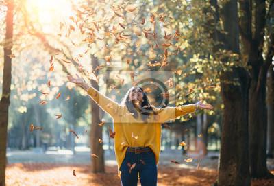 Fototapeta Przypadkowa radosna kobieta ma zabawy rzucać opuszcza w jesieni przy miasto parkiem.