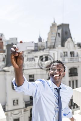 Przystojny biznesmen czarny biorąc selfie poza biurem