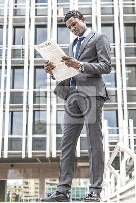 Przystojny biznesmen czarny czytania gazety na zewnątrz