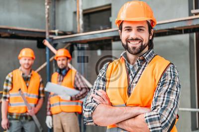 Fototapeta przystojny budowniczy uśmiechający się stojący na budowie ze skrzyżowanymi rękami, podczas gdy jego koledzy stoi niewyraźne na tle