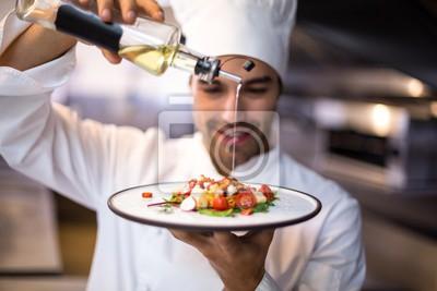Fototapeta Przystojny kuchni wlewanie oliwy z oliwek na posiłek