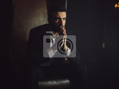 Fototapeta Przystojny mężczyzna z brodą w klasycznym garniturze siedzi w skórzanym fotelu i patrzy w kamerę.