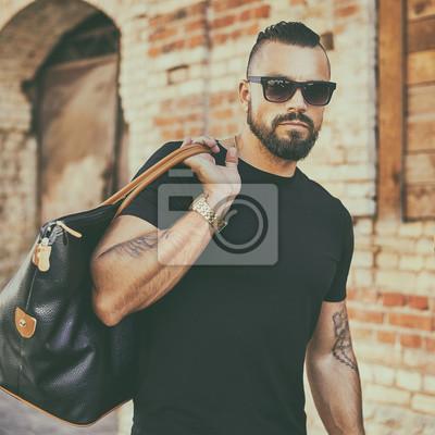Fototapeta Przystojny mężczyzna z brodą w okularach słonecznych i trzymając czarną torbę
