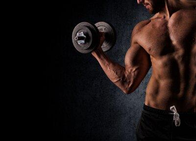Fototapeta Przystojny muskularny mężczyzna pracuje obecnie z hantle na czarnym tyłu