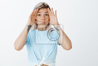 Puk puk. Portret uroczej figlarnej studentki w przyciętym topie z wytatuowanymi ramionami, trzymająca dłonie w pobliżu zaciśniętych i składanych warg, bawi się z młodszą siostrą lub wygłupia się z nud