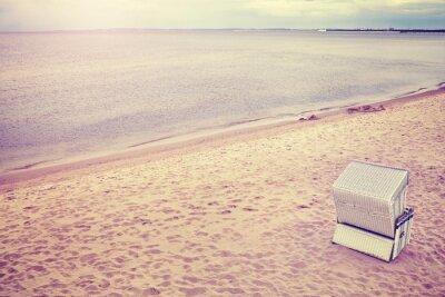 Fototapeta Purpurowy stonowanych kapturem kosz wiklinowy krzesło na pustej plaży.