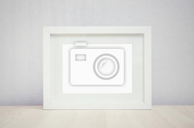 Fototapeta puste białe ramki na zdjęcia na ścianie i drewna tabeli