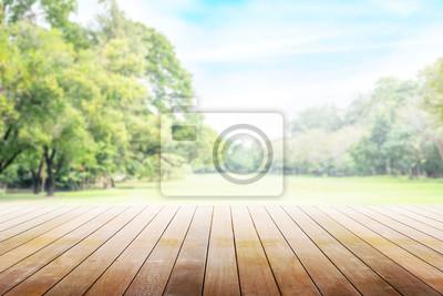 Fototapeta Pusty drewniany stół z przyjęciem w ogrodowym tle zamazującym.