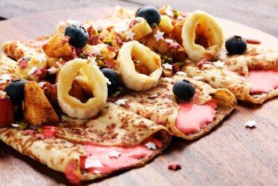 Pyszne domowe smaczne naleśniki lub naleśniki z jabłkiem, bananem i jagodami.