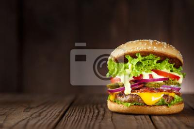 Fototapeta Pyszny burger z boczkiem, ogórkami, sałatą, serem, cebulą i pomidorami na ciemnym tle drewniane