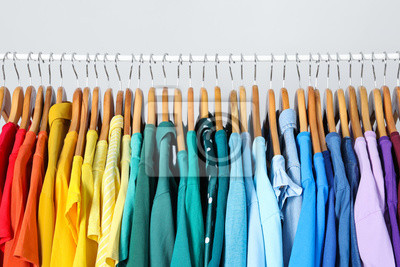 Fototapeta Rack with bright clothes on light blue background. Rainbow colors