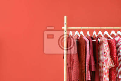 Fototapeta Rack with hanging clothes on color background