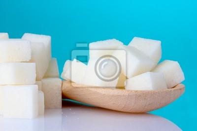 rafinowany cukier w drewnianą łyżką na niebieskim tle