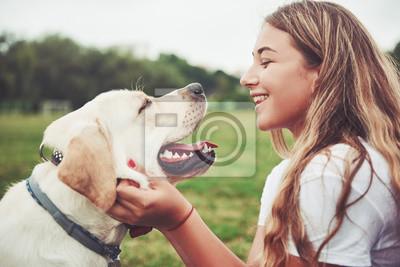 Fototapeta Rama z piękną dziewczyną z pięknym psem w parku na zielonej trawie.