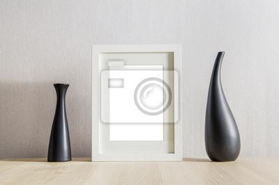 Fototapeta Ramka na zdjęcia z wazonie na drewnianym stole.