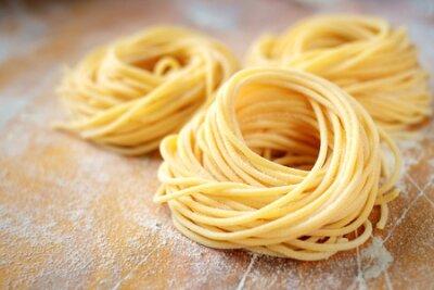 Fototapeta raw homemade spaghetti nest with flour on a wooden table. fresh Italian pasta