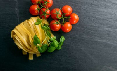 Fototapeta Raw yellow italian pasta pappardelle, fettuccine or tagliatelle close up. Egg homemade dry ribbon noodles, long rolled macaroni or uncooked spaghetti with tomatoes and basil top view