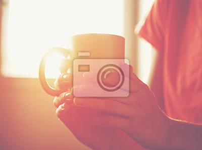 Ręce trzyma filiżankę gorącej herbaty lub kawy w porannym słońcu